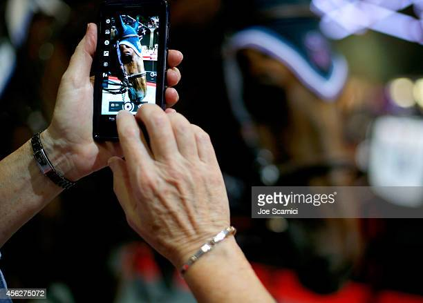 A guest takes a picture of a horse in the village area during the Longines Los Angeles Masters at Los Angeles Convention Center on September 28 2014...