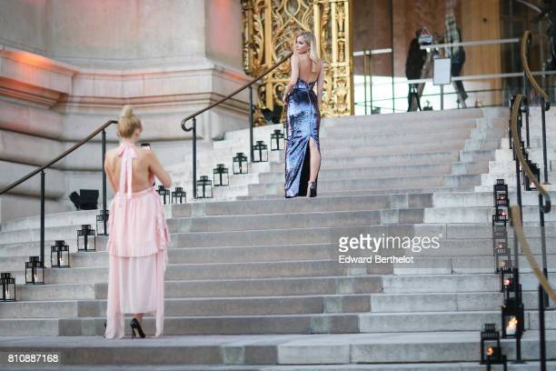 A guest takes a picture of another guest with her smartphone outside the amfAR dinner at Petit Palais during Paris Fashion Week Haute Couture...