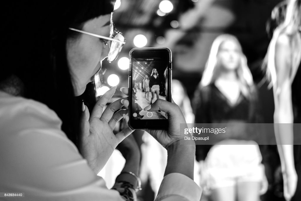 A guest takes a picture of models walking the runway during the Noon By Noor fashion show at New York Fashion Week: The Shows at Gallery 3, Skylight Clarkson Sq on September 7, 2017 in New York City.