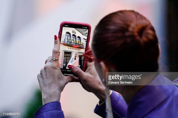 A guest takes a picture of the restaurant Lasserre with a mobile phone outside the Scandal A Paris JeanPaul Gaultier's New Fragance Launch Dinner...