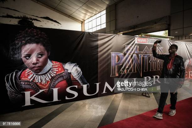 A guest takes a 'selfie' in front of an image of Kenyan actress Lupita Nyong'o before the African premier of the Marvel film 'Black Panther' in...
