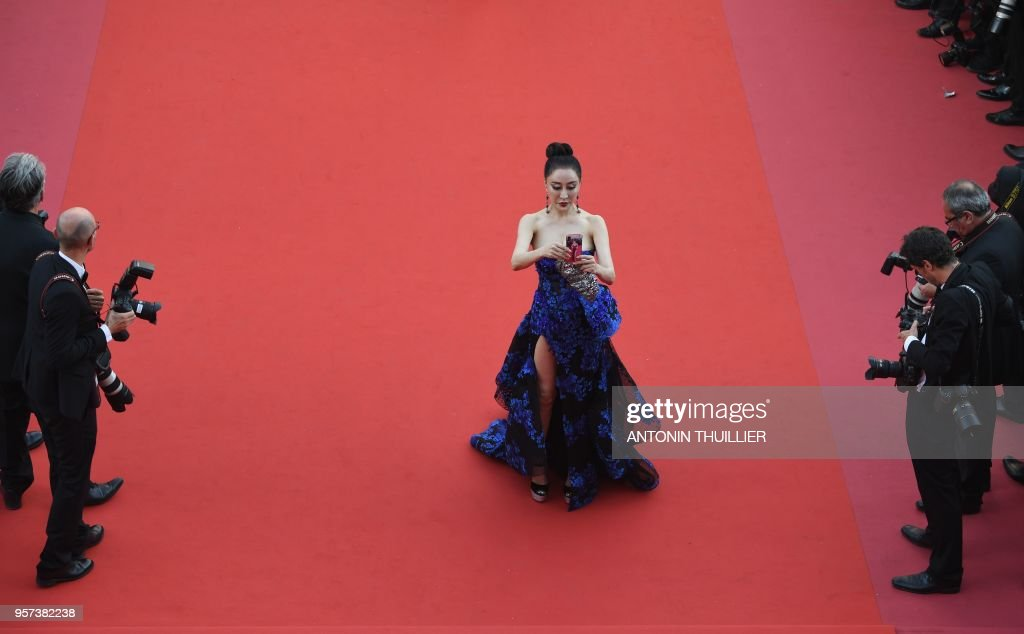 A guest takes a selfie photo as she arrives on May 8, 2018 for the screening of the film 'Todos Lo Saben (Everybody Knows)' and the opening ceremony of the 71st edition of the Cannes Film Festival in Cannes, southern France. - General Delegate of the Cannes Film Festival Thierry Fremaux banned selfie photos on the red carpet this year, hinting that offenders might be barred for 24 hours.