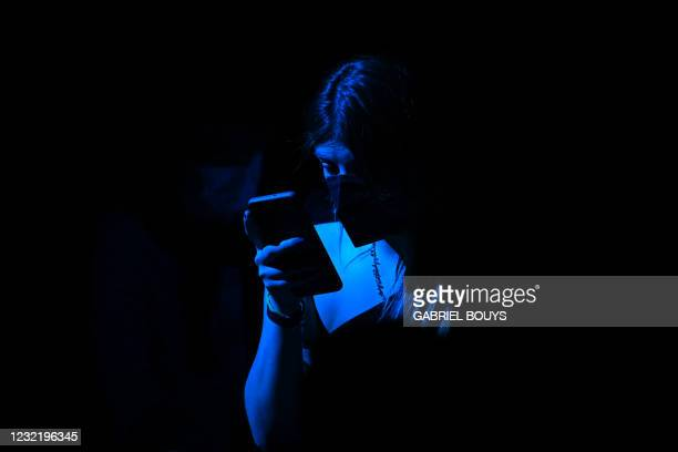 Guest takes a selfie with her smartphone during the Mercedes Benz Fashion Week in Madrid on April 8, 2021.