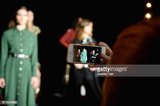 A guest takes of picture of the model on the runway for the Veronica Beard Fall 2018 presentation at Highline Stages on February 12 2018 in New York...