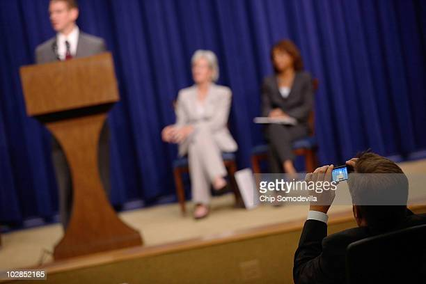A guest takes photographs of White House Office of National AIDS Policy Director Jeffrey Crowley Health and Human Services Secretary Kathleen...