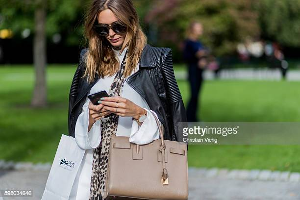 A guest texting with her phone wearing a black leather jacket and Saint Laurent bag outside Ida Sjöstedt during the second day of the Stockholm...