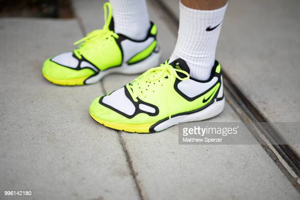 A guest trainer detail is seen on the street attending Men's New York Fashion Week wearing neon blue shorts with neon yellow sneakers on July 10 2018...