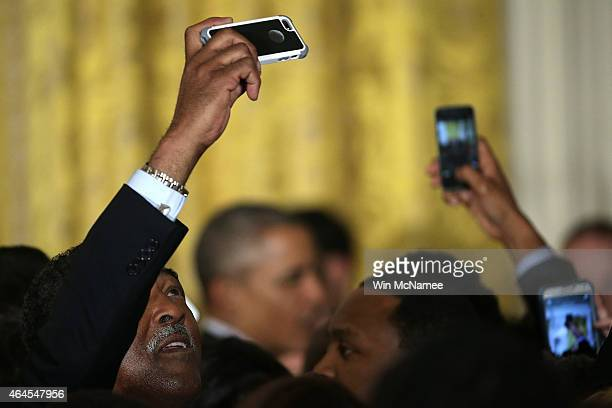 A guest tries to take a 'selfie' as US President Barack Obama departs after delivering remarks during an event in the East Room of the White House on...