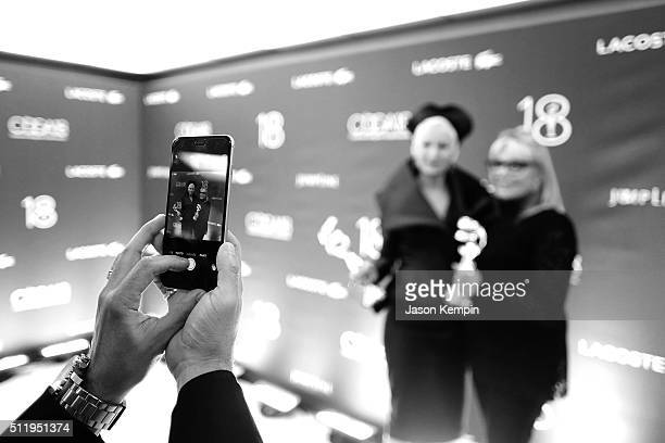 A guest uses a mobile phone to take a picture of costume Designers Lou Eyrich winner of the Outstanding Contemporary Television Series award for...
