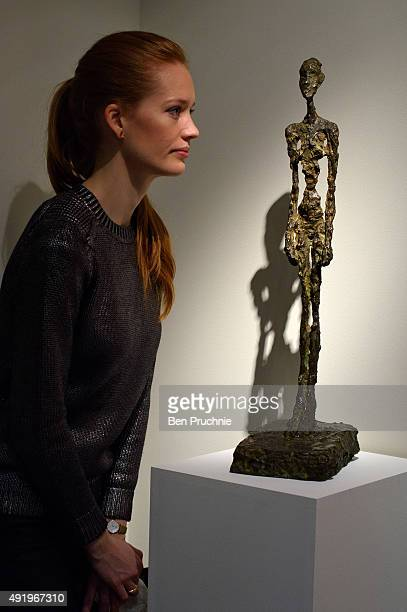A guest views 'Femme Debout' by artist Alberto Giacometti during the preview ahead of the artist's muse a curated evening sale in Christie's New York...