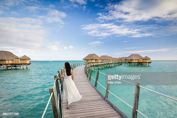 guest walking on the footbridge to water bungalows - タヒチ ストックフォトと画像