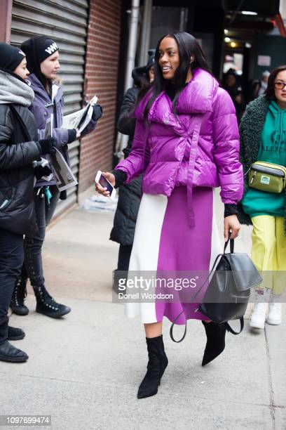 A guest walks outside of the Tibi show wearing a purple jacket white and purple skirt and black heels during New York Fashion Week on February 10...