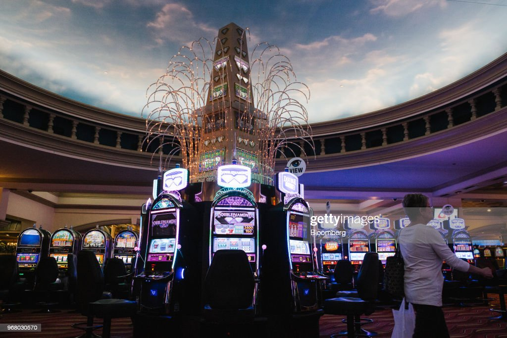 A guest walks past slot machines on the gaming floor during the launch of full-scale sports betting at Dover Downs Hotel and Casino in Dover, Delaware, U.S., on Tuesday, June 5, 2018. Delawarebecame the first U.S. state aside from Nevada to allow wagers on individual professional sporting contests, just three weeks after the U.S. Supreme Court freed states to do so. Photographer: Michelle Gustafson/Bloomberg via Getty Images