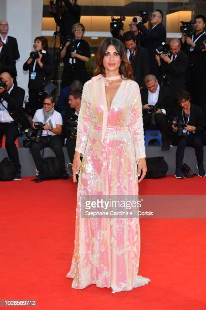 A guest walks the red carpet ahead of the 'At Eternity's Gate' screening during the 75th Venice Film Festival at Sala Grande on September 3 2018 in...