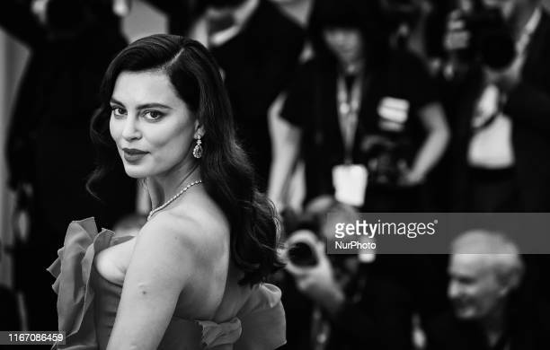 Image was converted to black and white A guest walks the red carpet ahead of the closing ceremony of the 76th Venice Film Festival at Sala Grande on...