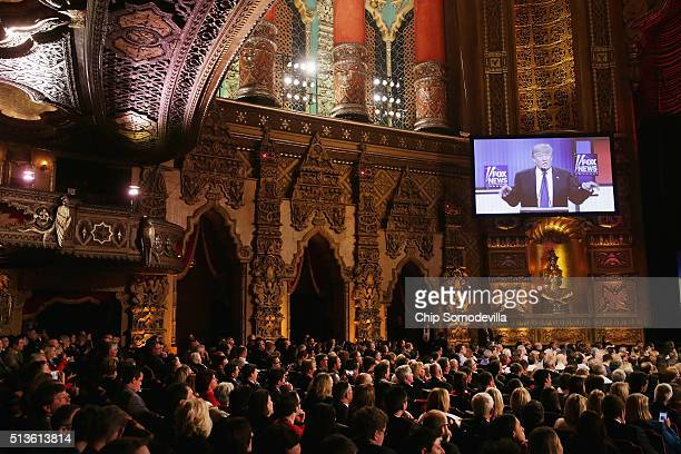 Guest watch as Republican presidential candidate Donald Trump participates in a debate sponsored by Fox News at the Fox Theatre on March 3, 2016 in...