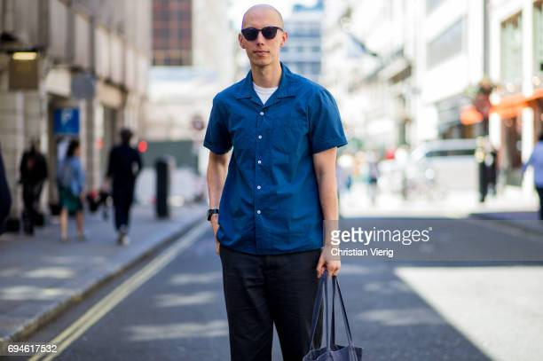 A guest weairng a navy button shirt with short sleeves hand bag during the London Fashion Week Men's June 2017 collections on June 10 2017 in London...