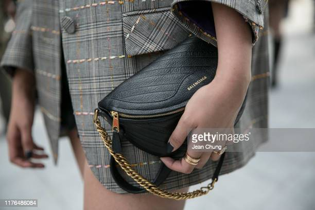 Guest wearing a Balenciaga bag is seen during the Seoul Fashion Week 2020 S/S at Dongdaemun Design Plaza on October 18, 2019 in Seoul, South Korea.