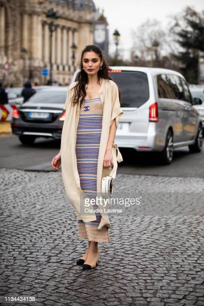Guest, wearing a beige and blue Chanel dress, beige long shirt, black and white bag and nude and black heels, is seen outside Chanel on Day 9 Paris...