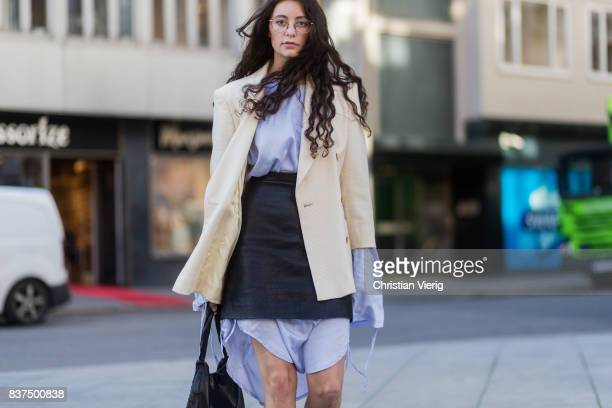A guest wearing a beige blazer oversized button shirt leather mini skirt outside byTiMo on August 22 2017 in Oslo Norway