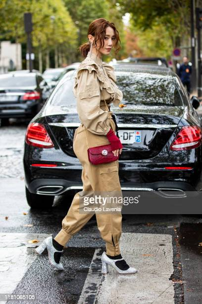 Guest, wearing a beige blouse, beige cargo pants and beige corset, burgundy bag and silver heels, is seen outside the Miu Miu show during Paris...