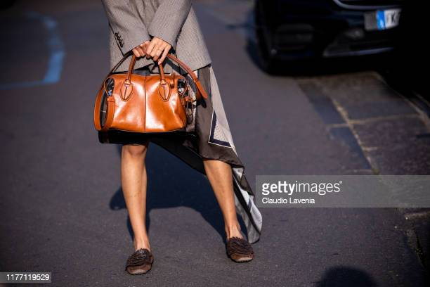 Guest, wearing a beige checked blazer, printed mini skirt, brown loafers and tan Tod's bag, is seen outside the Tod's show during Milan Fashion Week...