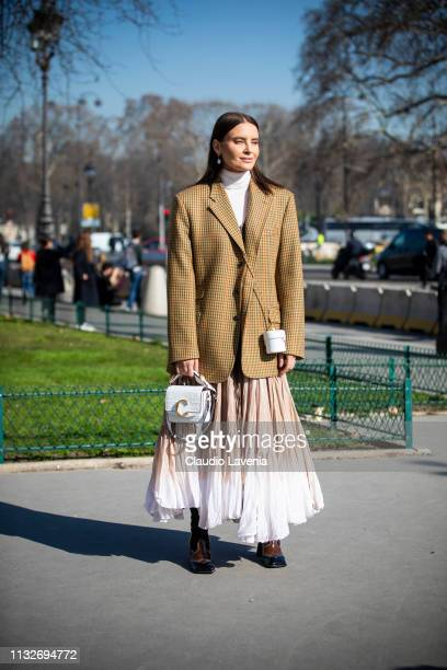 A guest wearing a beige checked blazer white turtleneck top beige and white maxi skirt and white Chloe bag is seen outside Maison Margiela on Day 3...