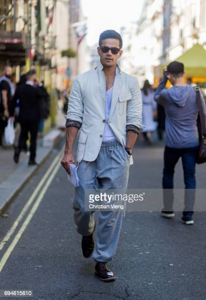A guest wearing a beige jacket and jogger pants during the London Fashion Week Men's June 2017 collections on June 10 2017 in London England