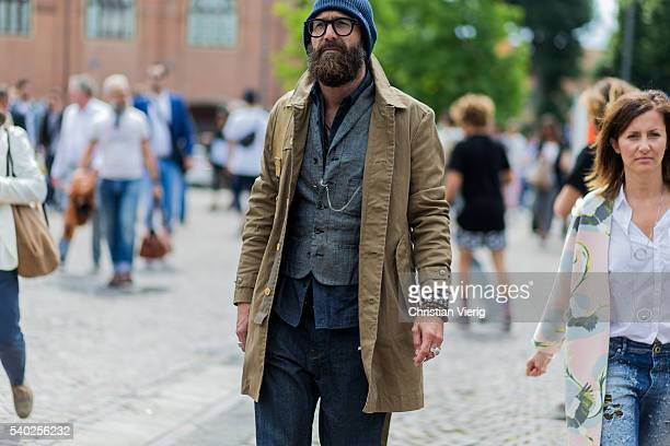 Guest wearing a beige jacket and navy hat during Pitti Uomo 90 on June 14 in Florence, Italy