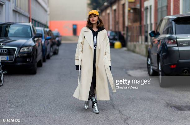 A guest wearing a beige trench coat Adidas hoody yellow flex cap outside Gucci on February 22 2017 in Milan Italy