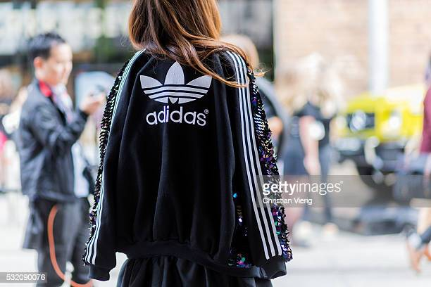 A guest wearing a black Adidas sweater sport jacket outside Yuxin at MercedesBenz Fashion Week Resort 17 Collections at Carriageworks on May 18 2016...