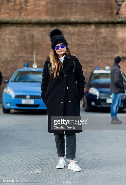 A guest wearing a black beanie black wool coat grey denim jeans white sneaker on January 10 2017 in Florence Italy
