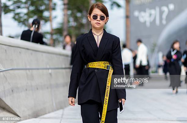 A guest wearing a black blazer with a yellow Off White belt attends day 5 of HERA Seoul Fashion Week on October 21 2016 in Seoul South Korea