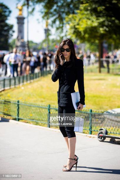 A guest wearing a black Chanel top black pants and black sandals is seen outside Chanel show during Paris Fashion Week Haute Couture Fall/Winter...