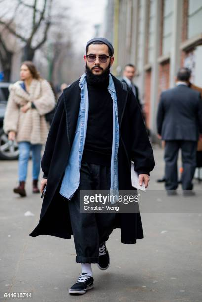 A guest wearing a black coat Vans denim shirt outside Fendi during Milan Fashion Week Fall/Winter 2017/18 on February 23 2017 in Milan Italy