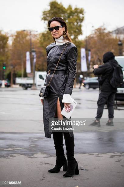 A guest wearing a black leather midi dress black over the knees boots and Chanel black bag is seen before the Chanel show on October 2 2018 in Paris...
