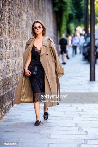 Guest, wearing a black midi dress with lace details, black bag, black loafers and beige trench coat, is seen outside VALENTINO show during Paris...