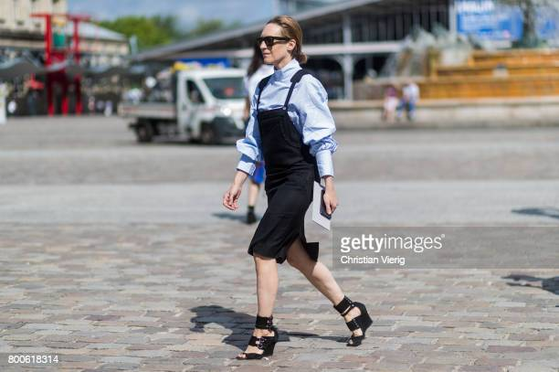 A guest wearing a black overall dress button shirt heeled sandals outside Sacai during Paris Fashion Week Menswear Spring/Summer 2018 Day Four on...