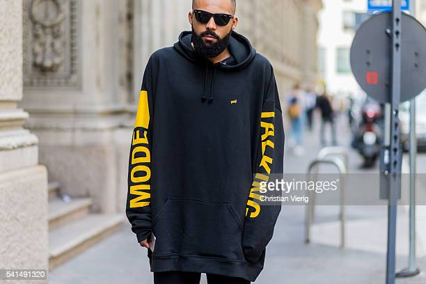 A guest wearing a black oversized hoody outside Ferragamo during the Milan Men's Fashion Week Spring/Summer 2017 on June 19 2016 in Milan Italy