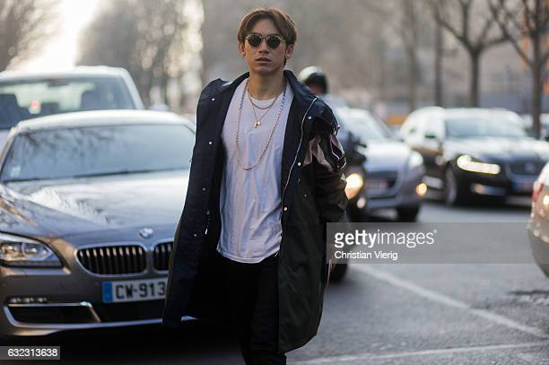 A guest wearing a black parka white tshirt outside Dior Homme on January 21 2017 in Paris France