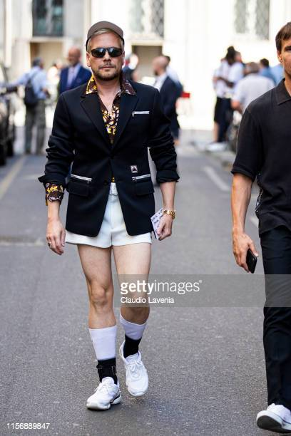 A guest wearing a black Prada blazer brown printed shirt white shorts white hat and white sneakers is seen outside Giorgio Armani show during the...