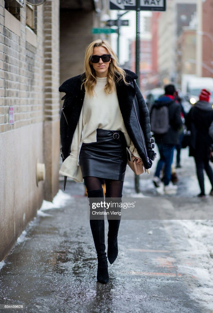 A guest wearing a black sheepskin leather jacket, white knit, black skirt, tights outside Noon by Noor on February 9, 2017 in New York City.