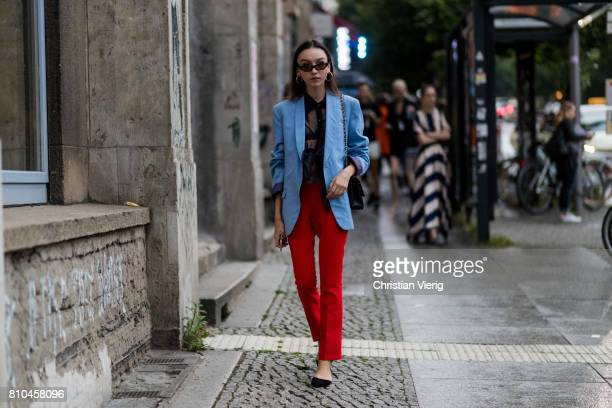 A guest wearing a black sheer top blue blazer red pants outside Prabal Gurung during the MercedesBenz Fashion Week Berlin Spring/Summer 2018 at...