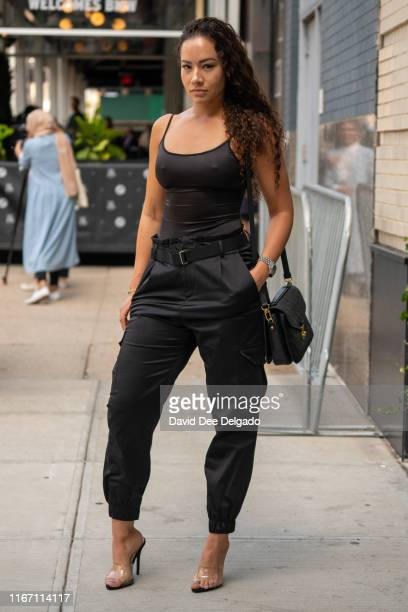Guest wearing a black spaghetti strap tank top, black pants, and translucent heels is seen during New York Fashion Week at Spring Studios on...