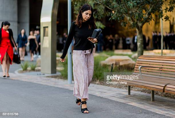 A guest wearing a black sweater and pink dress and sandals outside Toni Maticevski at MercedesBenz Fashion Week Resort 17 Collections at Barangaroo...