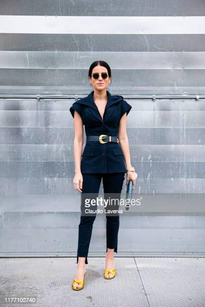 A guest wearing a black top black pants gold heels and green bag is seen outside the DROME show during Milan Fashion Week Spring/Summer 2020 on...