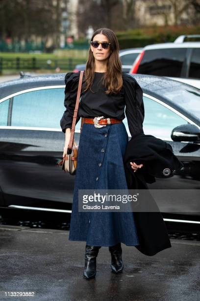 Guest, wearing a black top, denim maxi skirt, black boots, red belt and beige Loewe bag, is seen outside Haider Ackermann on Day 6 Paris Fashion Week...