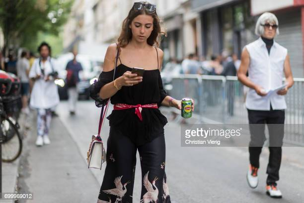 A guest wearing a black top red bandana as scarf white Gucci bag wide leg pants with print outside Dries van Noten during Paris Fashion Week Menswear...