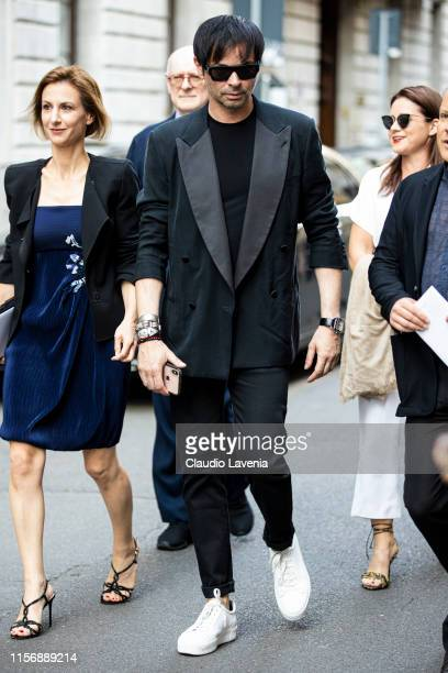 Guest, wearing a black t-shirt, black suit and white sneakers, is seen outside Giorgio Armani show, during the Milan Men's Fashion Week Spring/Summer...
