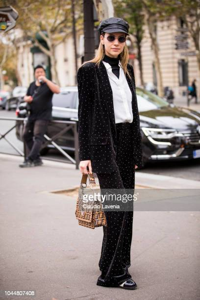 A guest wearing a black turtleneck underneath a white shirt black blazer with matching pants black leather baker boy hat and Fendi bag is seen before...